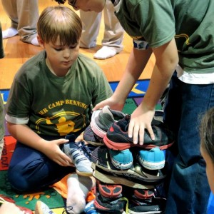 two boys stacking shoes